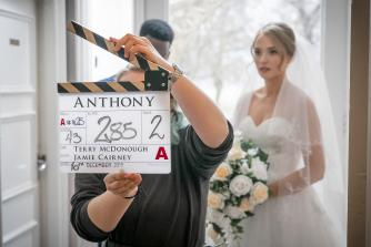 Behind the scenes photo of Anthony featuring clapperboard
